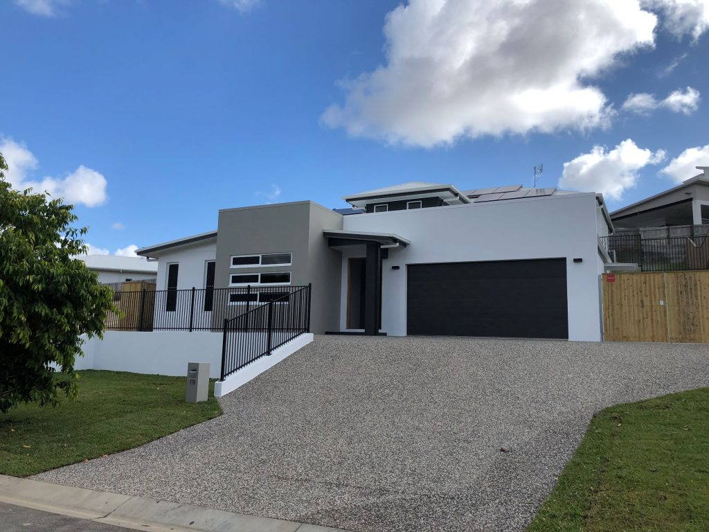 Sloping block, salt and pepper driveway, retaining wall, aluminium balustrading, split level home
